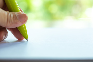 Woman's left Hand holding a yellow pen, writing letter on white paper, Bokeh green garden background, Notebook, Close up & Macro shot, Selective focus, Communication, Stationery concept