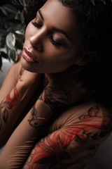 Fototapete - Glamour portrait of a metis young woman with perfect smooth glowing mulatto skin, full lips and fresh makeup on her face. Sensual and seductive african american female model is posing in the foliage
