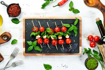 Cherry tomatoes, mozzarella and basil. Italian snacks. Caprese Top view. Free space for your text.