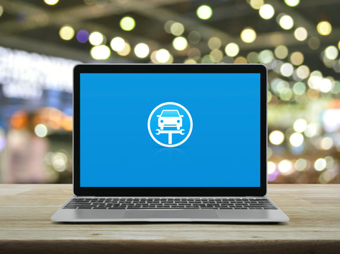 Service fix car with wrench tool flat icon on modern laptop computer on wooden table over blur light and shadow of shopping mall, Business repair car online concept