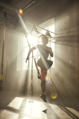 Professional training. Full-length of young athletic woman in sports clothing training legs with trx fitness straps in the gym.