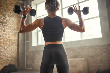 Great workout. Back view of young athletic woman in sportswear exercising with dumbbells while standing in front of window at gym.