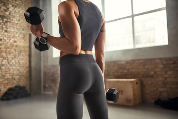 Perfect in everything. Close up of athletic woman with tattoo on her hand wearing sportswear and exercising with dumbbells while standing in front of window at gym.