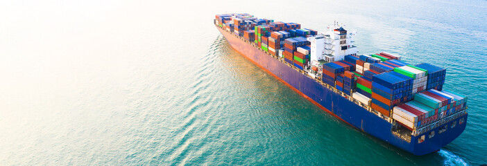 Aerial side view container ship carrying container in import export business logistic and transportation of international by container ship in the open sea, with copy space. Fotomurales