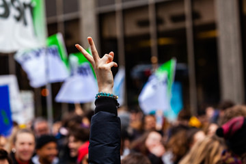 V gesture at environmental protest. A woman's arm is held in the air showing two fingers for peace, as ecological activists are seen marching in a city center.