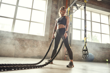 CrossFit training. Young athletic woman with perfect body doing crossfit exercises with a rope in the gym. Fototapete