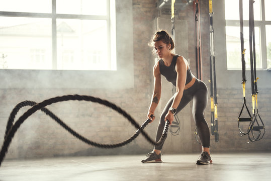 Preparing for the competition. Young athletic woman with perfect body doing crossfit exercises with a rope in the gym.