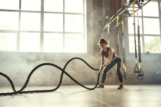 Strong and beautiful. Young athletic woman with perfect body doing crossfit exercises with a rope in the gym.