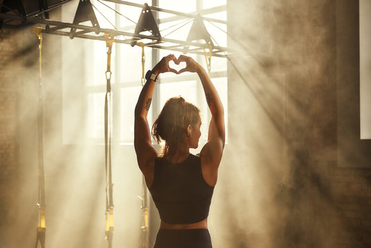 I love active life. Back view of young athletic woman in black sport clothing making heart shape with her hands while training in dark gym