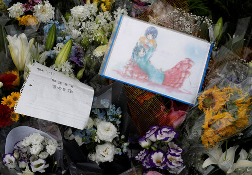 Flowers and a drawing with anime characters dedicated to the victims of the fire are seen left outside the Kyoto Animation building which was torched by arson attack, in Kyoto