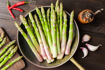 Asparagus in rustic pan on wooden background. Top view