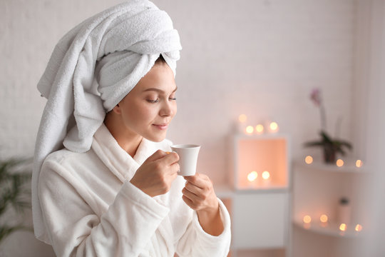 Beautiful young woman with cup of tea relaxing in spa salon