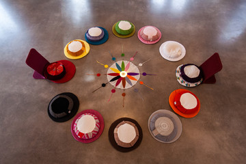 Sacred items form circle in prayer room. A high angled view on the twelve colors of the Native American wheel symbology, laid on the floor inside a religious hall, ready for devotees to worship.
