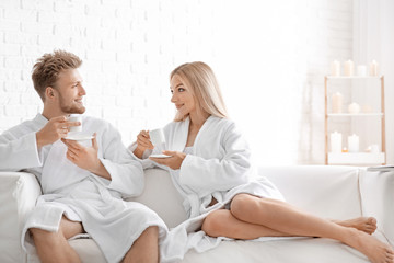 Wall Mural - Happy young couple in bathrobes drinking coffee at home
