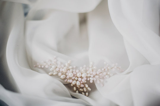 Stylish tender pearl hairpin on soft white tulle in morning light in hotel room. Bridal accessories for the wedding day. Modern jewelry. Morning preparations