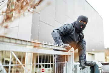 Einbrecher steigt über Zaun von Industrie Firma - fototapety na wymiar