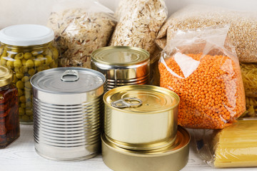 Various canned food and raw cereal grains on a table.