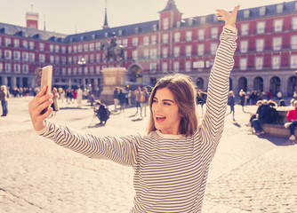Attractive happy young tourist woman taking selfie or video in Madrid Spain having fun