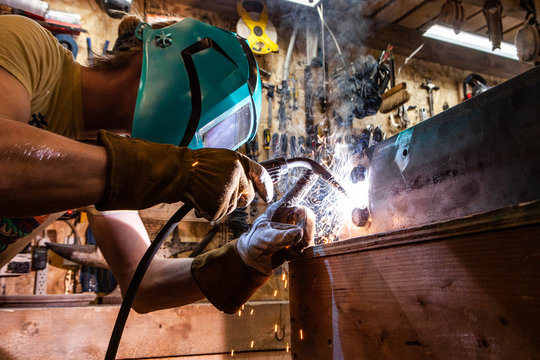 Metalworker operates spot welder indoors. A closeup view of a skilled tradesman operating a metal inert gas welder to join the corners of two steel beams. Process of a metalworker at work.
