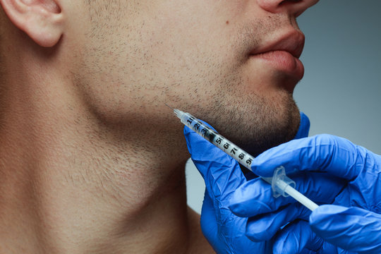 Close-up profile portrait of young man isolated on grey studio background. Filling botox surgery procedure. Concept of men's health and beauty, cosmetology, self-care, body and skin care. Anti-aging.