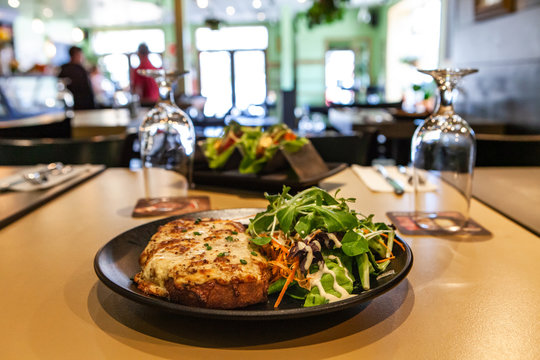 Fresh lunch prepared in restaurant. A closeup view of croque monsieur, a toasted cheese sandwich served with crunchy salad, on a table inside a bistro, blurry patrons and tables in background.