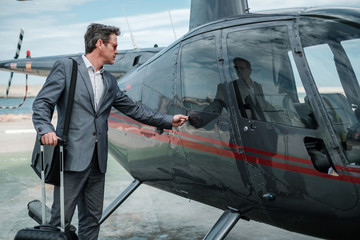 Businessman talking on cellphone near private helicopter