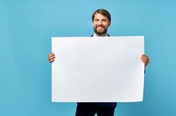 Fototapeta man holding a white blank on a blue background obraz