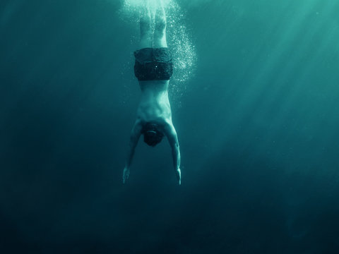 Man jumping into the water. Underwater shot. Vacation, sports and active lifestyle concept.