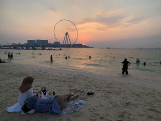 People enjoy the sunset on the beach at Jumeirah Beach Residence in Dubai