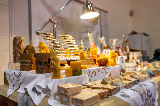 Seasonal products sold at Xmas market. Handcrafted candles and bars of soap are seen on a quaint stand at a local Christmas fair, traditional gifts with copy space on the right.