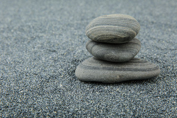 Photo sur Plexiglas Zen pierres a sable background of sea smooth stones. pyramid of stones on gray sand background with free space