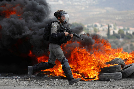 Israeli border police member runs past burning tires during a Palestinian protest in the village of Kofr Qadom in the Israeli-occupied West Bank
