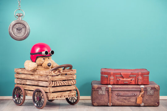 Teddy Bear toy in red helmet with  goggles in hand made wooden box with retro car wheels concept, antique leather travel luggage, old clock front mint blue background. Vintage style filtered photo
