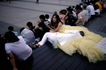 A couple rest on the steps during their wedding photo session on the Bund in Shanghai