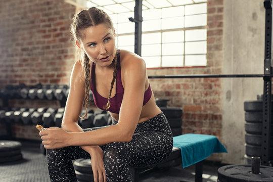 Fitness woman eating energy bar at gym