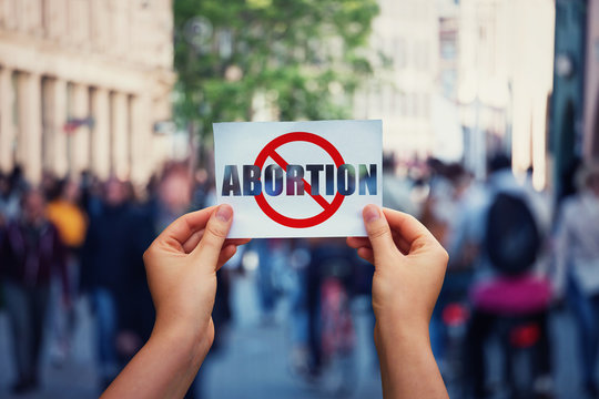 Activist hands holding a banner with stop abortion message over a crowded street background. Social awareness concept, humanity problems say no to abortion. Fetus rights law and reproductive justice