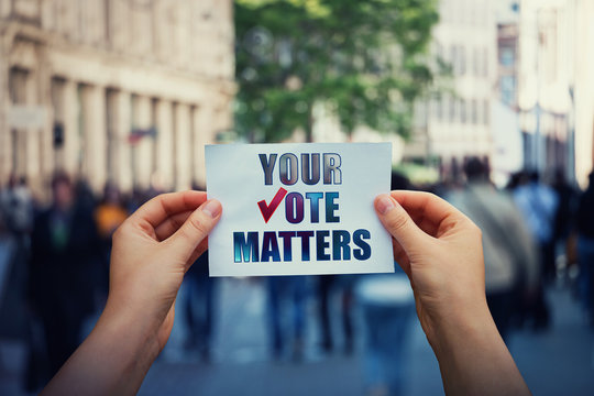 Hands hold a paper sheet with the message your vote matters over a crowded street background. People legal and democratic rights, every voice counts. Election campaign and electoral agitation concept