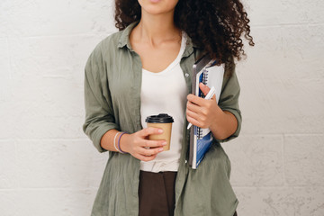 Close up photo of student girl with dark curly hair in khaki shirt holding laptop with notepad and cup of coffee to go in hands