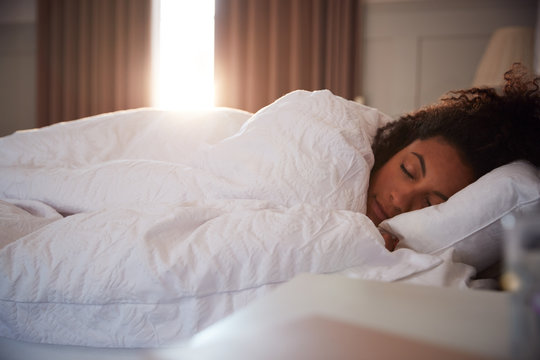 Peaceful Woman Asleep In Bed As Day Break Through Curtains