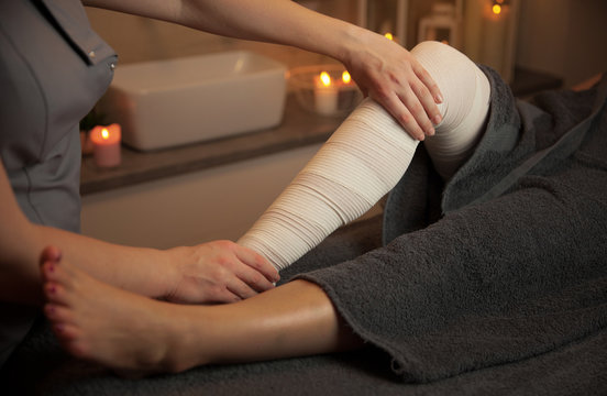 bandages legs lymphatic drainage massage for a patient with swelling effect in beauty salon background with candles