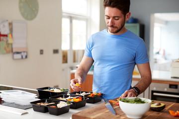 Man Preparing Batch Of Healthy Meals At Home In Kitchen Papier Peint