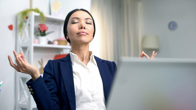 Young business lady meditating front laptop reducing stress, relaxing technique
