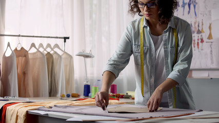 Professional designer transferring pattern samples to fabric, clothes making
