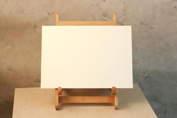 Caballete con lienzo en blanco con fondo industrial de cemento
