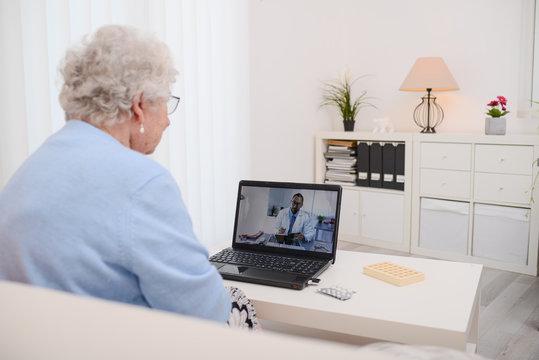 elderly senior woman, having a remote medical consultation with her doctor over internet computer telemedecine diagnostic
