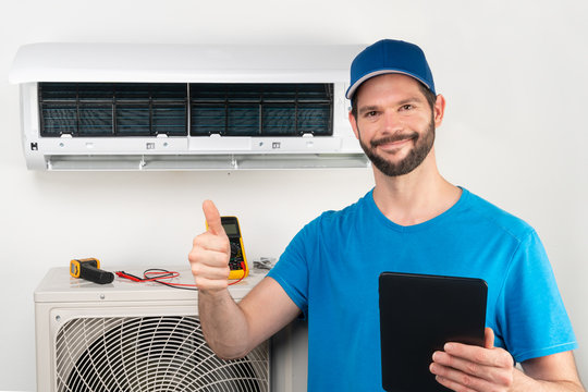Installation service fix  repair maintenance of an air conditioner indoor unit, by cryogenist technican worker giving thumbs up ready to go after commissioning in blue shirt  baseball cap