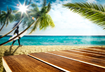 Wooden table top backround with beautiful calm ocean in distance. Some palm leaves above the wooden...