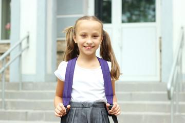 Cute schoolgirl with a school backpack in the schoolyard.
