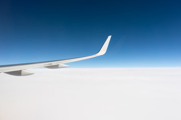Airplane wing above the cloud line Fotoväggar