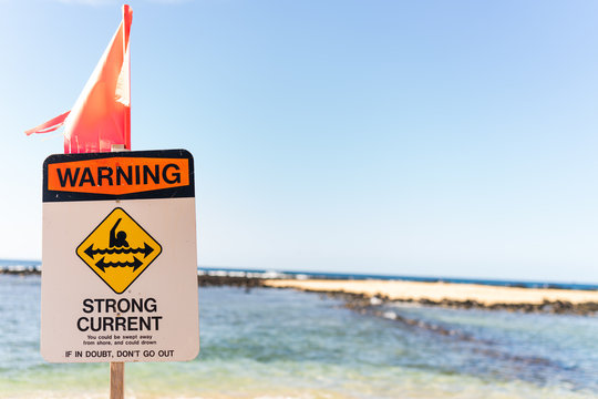 Sign warning about strong current on beach